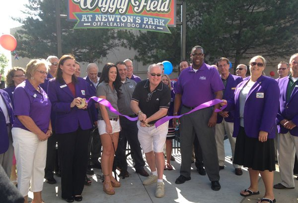 Jim Walsh cuts the ribbon at Wiggly Field in downtown Waterloo on Wednesday, surounded by the Cedar Valley Ambassadors. (Amie Steffeneicher, KWWL)