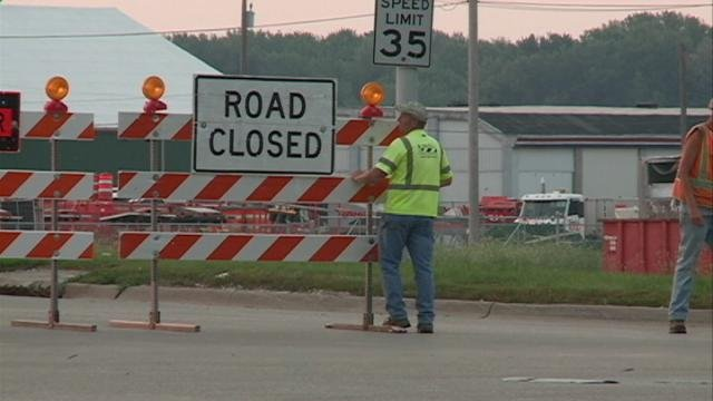 A worker places a sign, launching the 10-day Julien Dubuque/US Highway 20 bridge closure