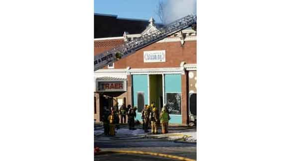 Firefighters work at a fire at Simply Blooming in Traer as smoke can be seen pouring from the roof. (Michael Crowe, KWWL)