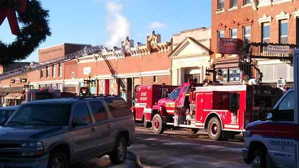 Firefighters work at a fire at Simply Blooming in Traer as smoke can be seen pouring from the roof. (Eric Lightner, KWWL)