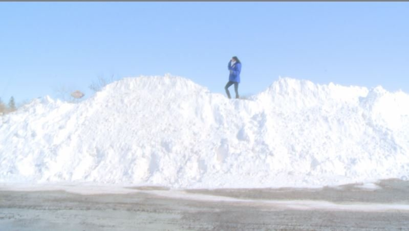 KWWL's Olivia Mancino stands atop a parking lot snow hill