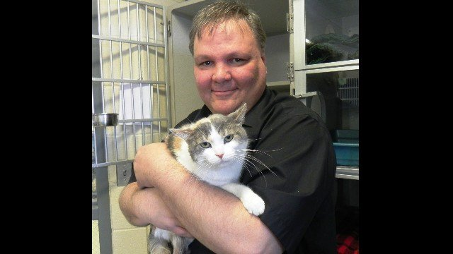 """Ken Avery holds his newly-adopted cat """"Winnie"""" after adopting her"""