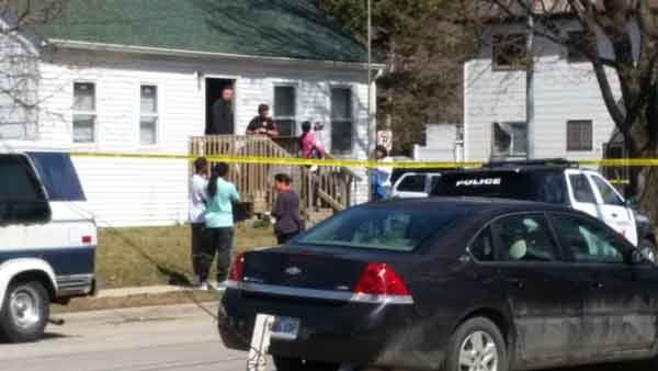 Witnesses and neighbors gather at a house on Mulberry Street in Waterloo where a 4-year-old boy was shot Thursday afternoon. (Bob Waters, KWWL)