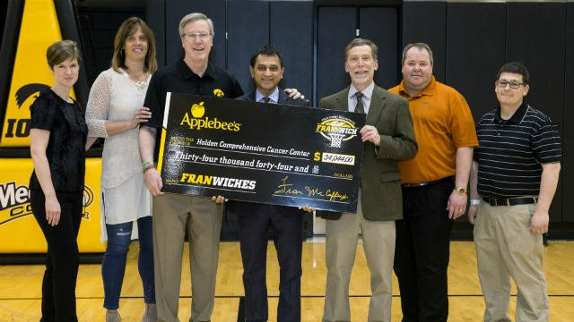 Fran & Margaret McCaffery with representatives of Applebee's present a check for $34,044 to representatives from the Holden Comprehensive Cancer Center