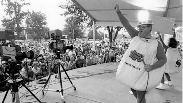 "On Aug. 22, 1985, Iowa Lottery employees Jeff Borron and Mary Kay Zaver wore ""moneybags"" costumes on a stage at the Iowa State Fair as they joined the crowd in cheering the start of lottery sales."