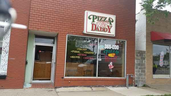 The front door of Pizza Daddy's on 1st Avenue in Cedar Rapids. The front glass door was busted and investigators were upstairs Tuesday morning. (Kaley Wasson, KWWL)