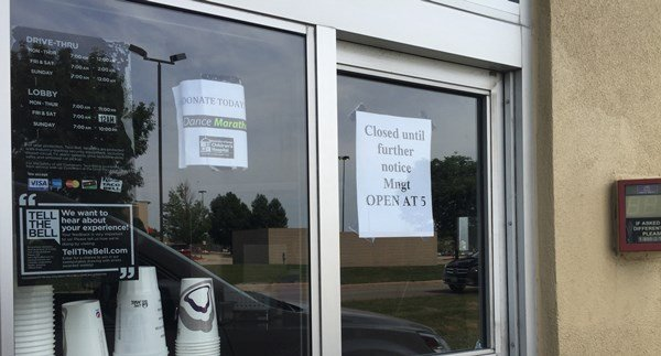 """Sign on the Taco Bell's drive-thru window says """"Closed until further notice ... Open at 5"""" on the morning of Tuesday, Aug. 4, 2015. (Lauren Moss, KWWL)"""