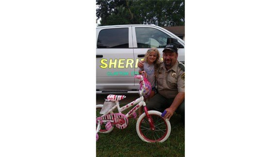Claire Goltz, left, poses with her new bicycle and Clayton County Sheriff Mike Tschirgi. (Courtesy Clayton County Sheriff's Office)