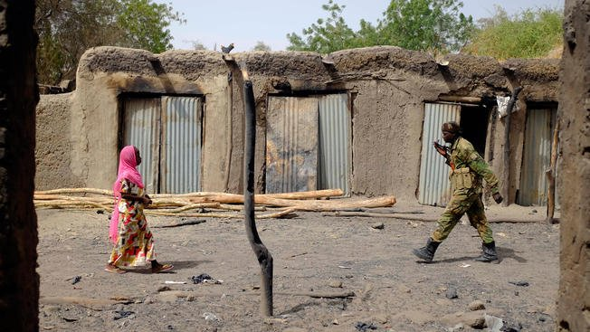 In this photo from Thursday, March 5, 2015, a Chadian soldier and a woman walk past burned stores in the Lake Chad shore village of N'Gouboua. Boko Haram militants arrived in N'gouboua before dawn on Feb. 13, marking the first attack of its kind on Chad.
