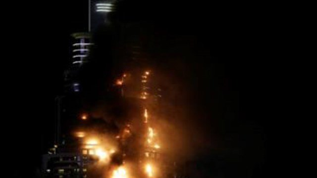 Smoke and flames pouring from a residential building, which also contains the Address Downtown Hotel, in Dubai, United Arab Emirates, Thursday evening, Dec. 31, 2015