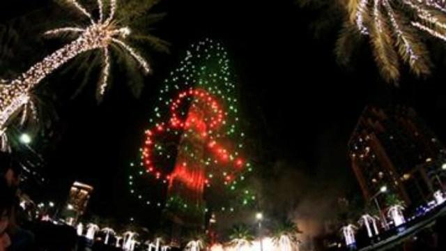 Fireworks illuminate the Burj Khalifa as a tower burns behind it in Dubai, United Arab Emirates on Friday, Jan 1, 2016