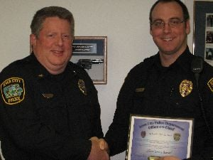 Iowa City Police Chief Sam Hargadine congratulates Officer Jeremy Bossard