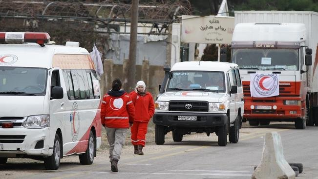 A convoy of aid from the Syrian Arab Red Crescent waits on the outskirts of besieged rebel-held Syrian town of Madaya, on January 14, 2016. The convoy of about 50 aid trucks left Damascus for the hunger-stricken Syrian town of Madaya where 40,000 resident