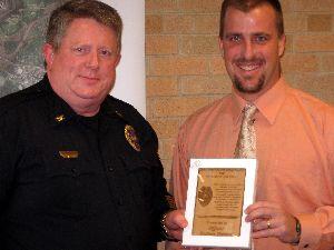 Police Chief Hargadine (left) presents the award to Investigator Zach Diersen (right)