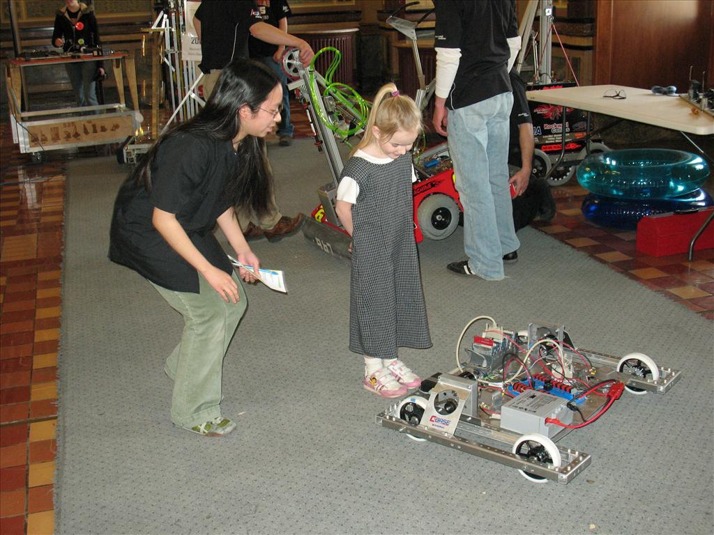Joanna Koa, 17, a member of Iowa City West High School's Robotics team, shows a girl the 2009 test robot