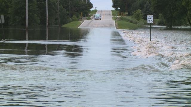 Never cross flooded roads. The moving water can wash your car... and the roadway... away.