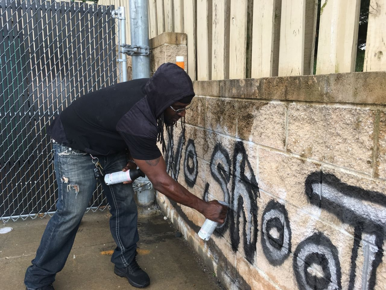 """In this Wednesday, Aug. 2, 2017, photo Tyree Colion spray paints the words """"No Shoot Zone"""" on a brick wall behind a convenience store, in a spot near where a 13-year-old girl was fatally shot in Baltimore County, Md. (AP Photo/Juliet Linderman)"""