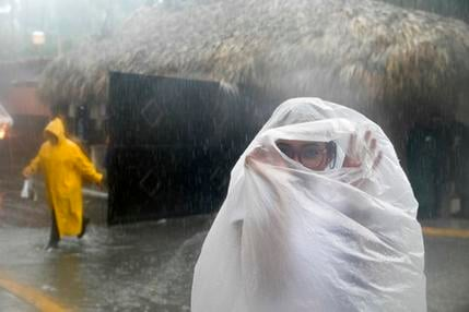 A woman covers herself with a plastic bag as she makes her way to work as Hurricane Maria approaches the coast of Bavaro, Dominican Republic, Wednesday, Sept. 20, 2017. (AP Photo/Tatiana Fernandez)