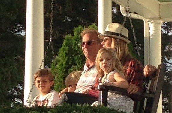 Kevin Costner enjoys a nostalgic moment, sitting on the Field of Dreams front porch swing.