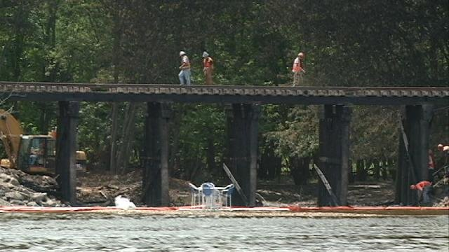 Canadian Pacific crews inspect and repair the fire-damaged railroad bridge Tuesday